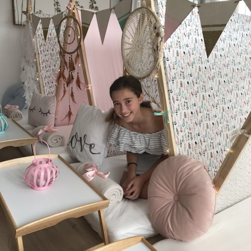 Happy girl looking out of teepee, slumber party by Angels Teepees Sydney